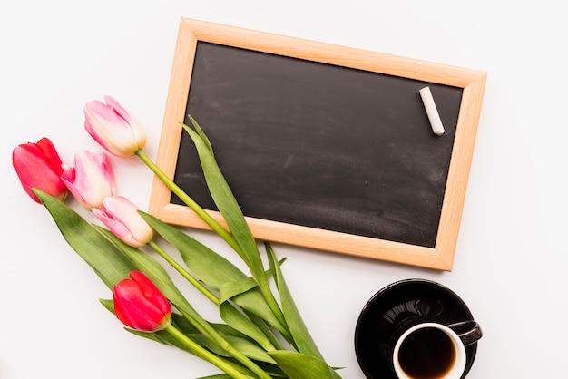 Heldere frisse bloemen op stelen in de buurt van schoolbord en een kopje drank