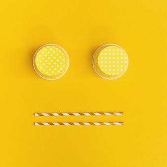 Heldere gele achtergrond met droevig glimlachgezicht van document het drinken rietjes en koppen. bovenaanzicht creatieve kleurrijke wenskaart.