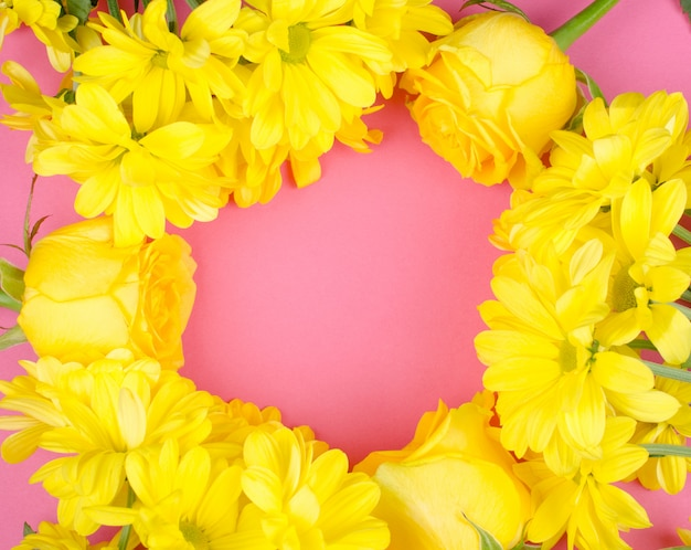 Heldere gele chrysantenbloemen en rozen die een achtergrond van het cirkelkader vormen