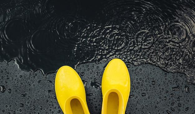 Heldere gele rubberlaarzen voor dames staan onder regendruppels op zwart