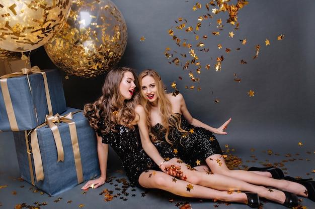 Heldere gelukkige momenten op het feest van twee geweldige jonge vrouwen in luxe zwarte jurken die chillen op de vloer. viering, plezier maken, cadeautjes, gouden tinsels, glimlachen.