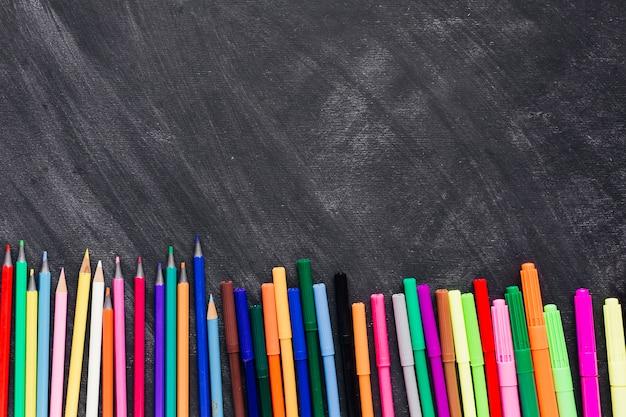 Heldere gevoelde pennen en potloden bij bodem van donkere achtergrond
