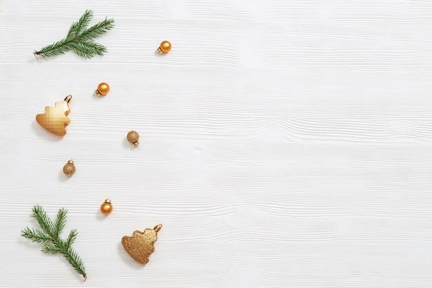 Heldere glanzende kleine kerstballen goudkleurig met natuurlijke groene dennenboomtak, nieuwjaarsdecor
