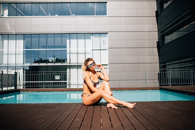 Heldere grappige vrouw ligt aan de rand van het zwembad