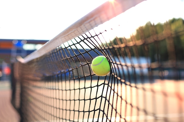 Heldere groenachtig gele tennisbal die het net raakt.