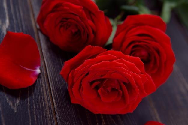 Heldere grote rozen met bloemblaadjes op een donkere houten tafel