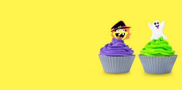 Heldere halloween cupcakes met groene en paarse room en spook en heks decor op gele achtergrond.