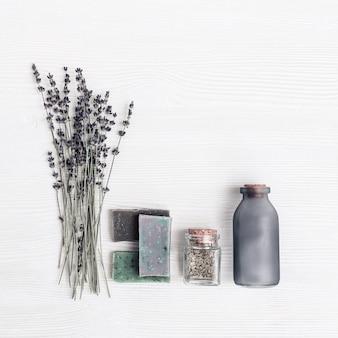 Heldere handgemaakte zeepstaven, gedroogde lavendelbloemen en glazen pot met geurige kruiden.