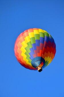 Heldere heteluchtballon in de blauwe lucht
