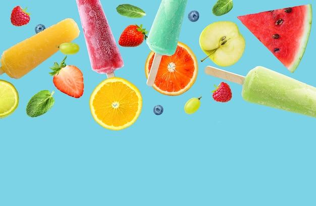 Heldere ijslollystokjes en fruit op aqua blauwe achtergrond. warm zomerconcept. ruimte kopiëren.