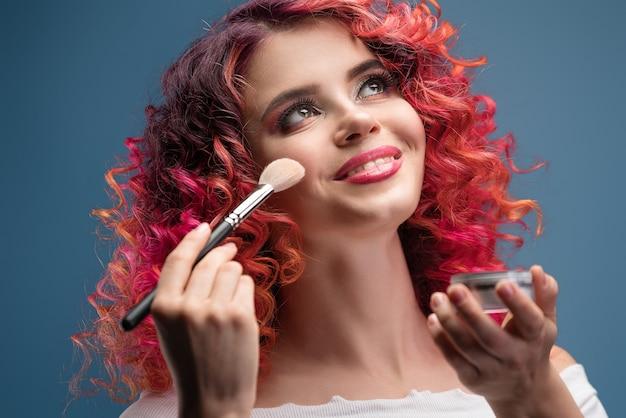 Heldere jonge vrouw met make-up borstel krullend rood haar