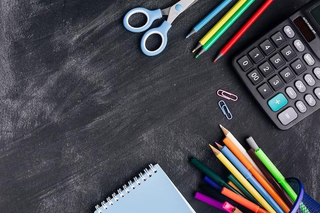 Heldere kantoorbehoeften en calculator op grijze achtergrond