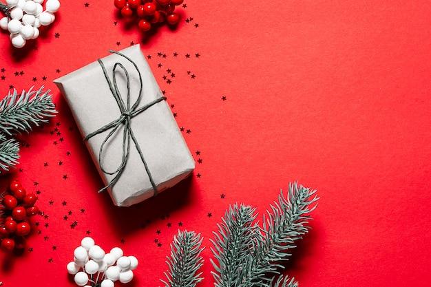 Heldere kerstmissamenstelling met giftdoos in kraftpapier, sparrentakken en decoraties op heldere rode achtergrond.