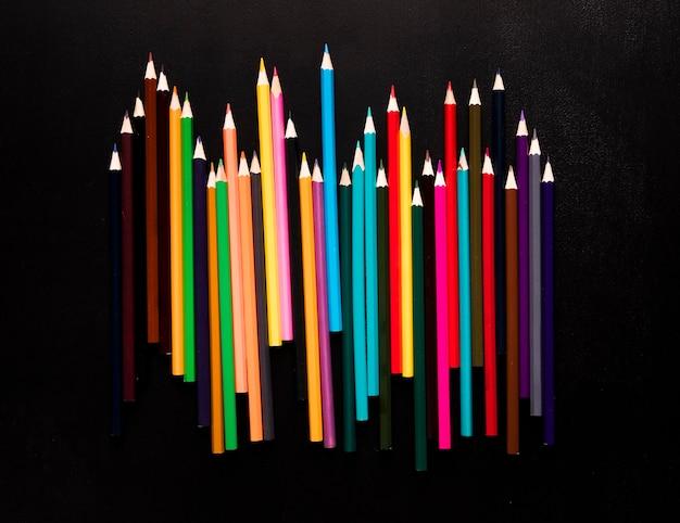 Heldere kleurenpotloden die op zwarte achtergrond worden geplaatst