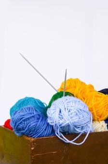 Heldere kleurrijke ballen van garen en breinaalden in een houten kist op witte achtergrond.