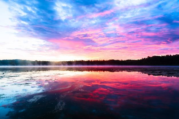 Heldere kleurrijke mistige zonsondergang op het meer met wolken en reflecties