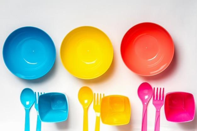 Heldere kleurrijke plastic kommen, borden en bestek