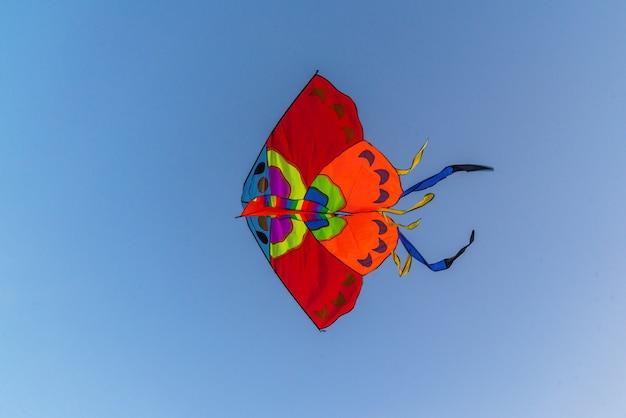 Heldere kleurrijke vlieger vliegen in de blauwe heldere hemel
