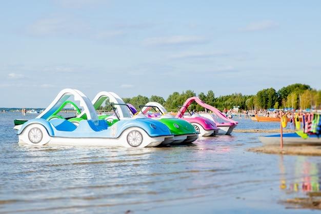 Heldere kleurrijke waterfietsen op het strand van het meer