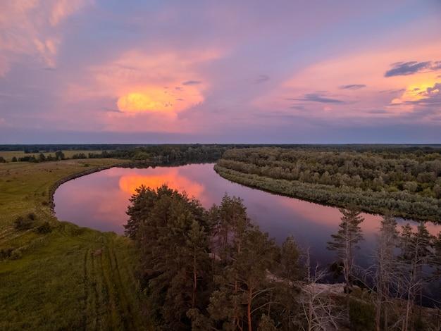 Heldere kleurrijke wolken boven de rivier na de zonsondergang