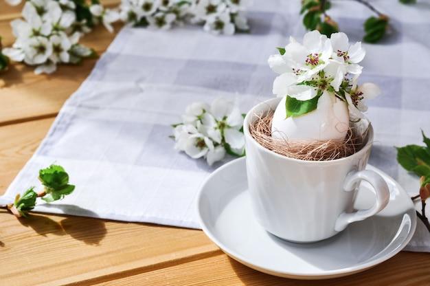 Heldere lente pasen samenstelling van natuurlijke bloemen in een wit ei in een cirkel op grijze tafellaken op zonnige dag.