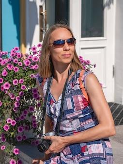Heldere levensstijl portret van lachende mooie vrouw zittend op borstwering met bloemen. trendy stijlvol meisje ontspannen. reis- en actief levensstijlconcept.