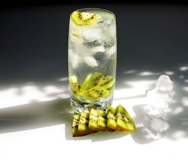 Heldere limonade met ijs en plakjes kiwi. zomer verfrissend koel drankje.