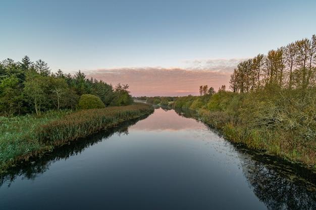 Heldere lucht ochtend op inny rivier met reflecties van lucht, bomen.