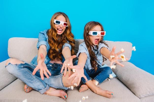 Heldere momenten van mooie jonge moeder met plezier met dochter op bank geïsoleerd op blauwe achtergrond. modieuze kijk in jeanskleding, popcorn naar de camera gooien, gekke positiviteit uitdrukken