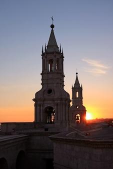 Heldere ondergaande zon schijnt door de klokkentoren van de basiliek kathedraal van arequipa, peru