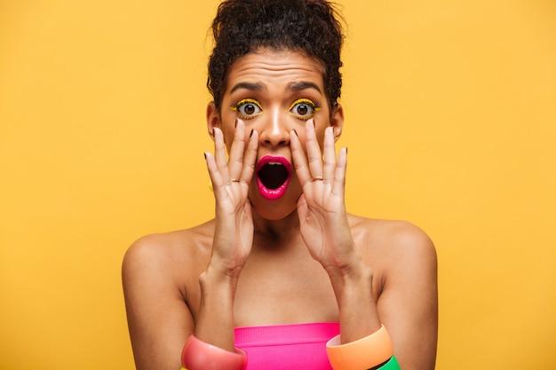 Heldere opgewekte modieuze afrikaanse amerikaanse vrouw die emotioneel of camera roept roept die handen zet bij mond geïsoleerd, over gele muur