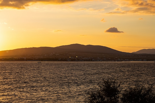 Heldere oranjegele zonsondergang bij de bergen en de kust van de zwarte zee