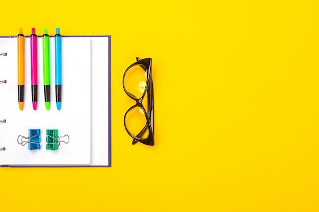 Heldere pennen, glazen en notitieboekje liggen geïsoleerd op gele achtergrond