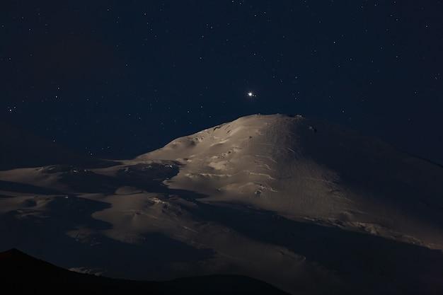 Heldere planeet jupiter met satellieten boven de besneeuwde top van de berg elbrus