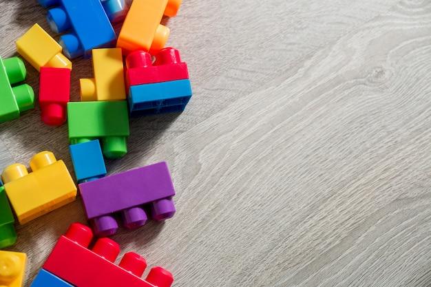 Heldere plastic bouwblokken op grijze houten achtergrond als achtergrond. speelgoed ontwikkelen. vroeg leren. bovenaanzicht. plat leggen