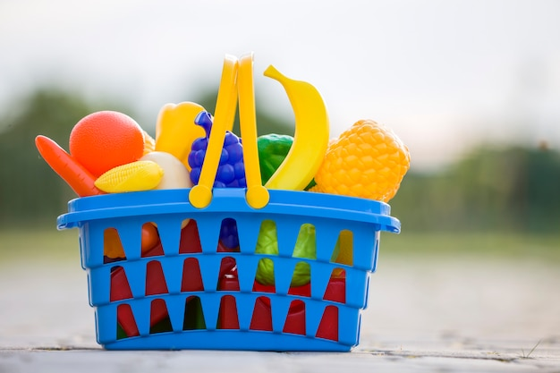 Heldere plastic kleurrijke mand met stuk speelgoed fruit en groenten in openlucht op zonnige de zomerdag.