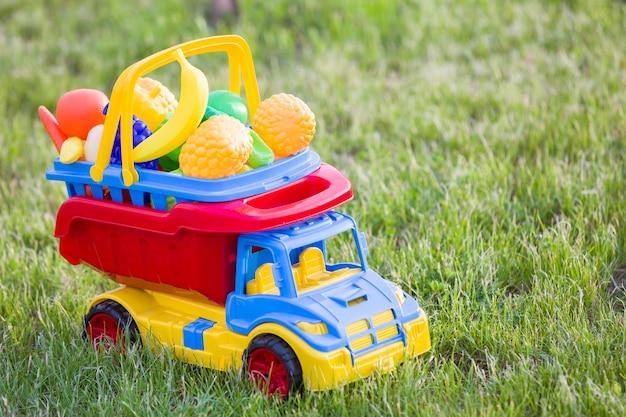 Heldere plastic speelgoedauto vrachtwagen dragende mand met speelgoed groenten en fruit.