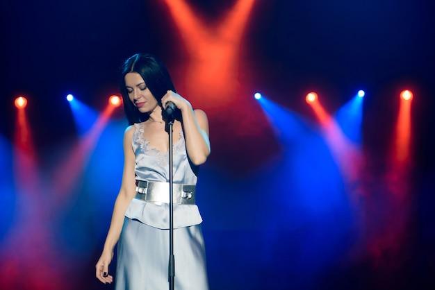 Heldere podiumverlichting. zanger zingen naar microfoon.