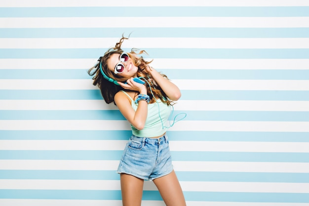Heldere positieve emoties van jonge vrolijke vrouw uitdrukken in bewegende luisteren naar muziek met koptelefoon op gestreepte muur. zomerlook, lang krullend donkerbruin haar, zonnebrillen, echte emoties.