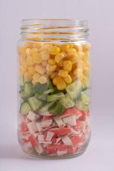 Heldere regenboogsalade van mais, komkommer en krabsticks. trends in gezond eten
