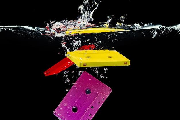Heldere retro audiocassette die in het water tegen zwarte dichte omhooggaand duikt