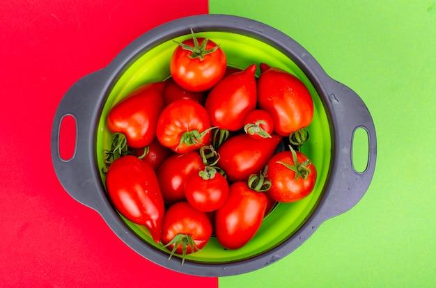 Heldere rijpe rode tomaten op gekleurde achtergrond, banner, behang. studiofoto.