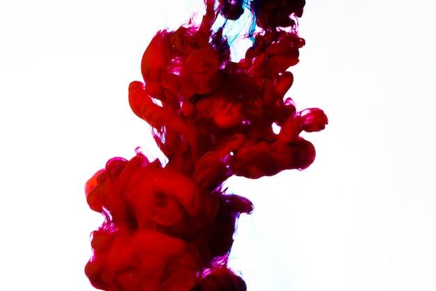 Heldere rode druppel inkt onder water