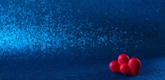 Heldere rode harten abstracte blauwe bokeh achtergrond heldere rode harten abstracte blauwe bokeh achtergrond. valentijnsdag textuur.
