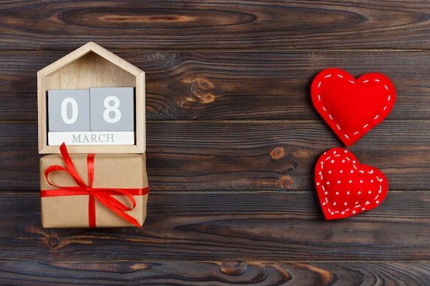Heldere rode harten met houten blok kalender en geschenkdoos