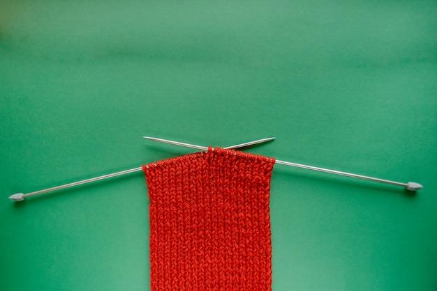 Heldere rode sjaal met breinaalden. op groene achtergrond. groen en rood contrast.
