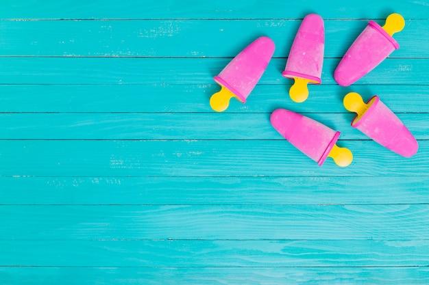 Heldere roze ijslollys op gele stokken op houten achtergrond