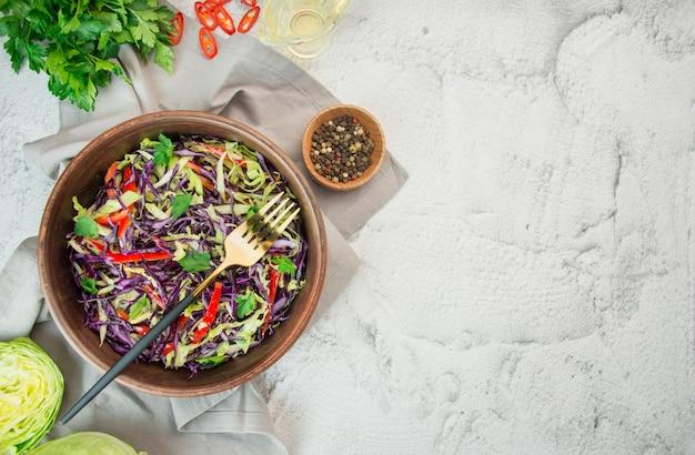 Heldere salade van paarse kool, witte kool, paprika in een plaat op een lichte tafel. lichte salade van verse groenten. voedsel achtergrond. vegetarisch gerecht. uitzicht van boven. kopieer ruimte