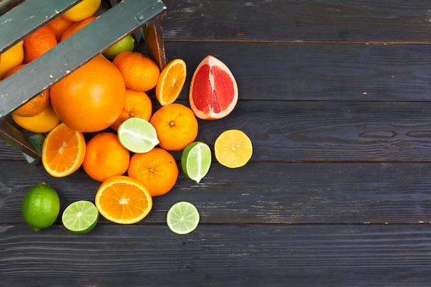 Heldere samenstelling van citrusvruchten op zwarte houten achtergrond