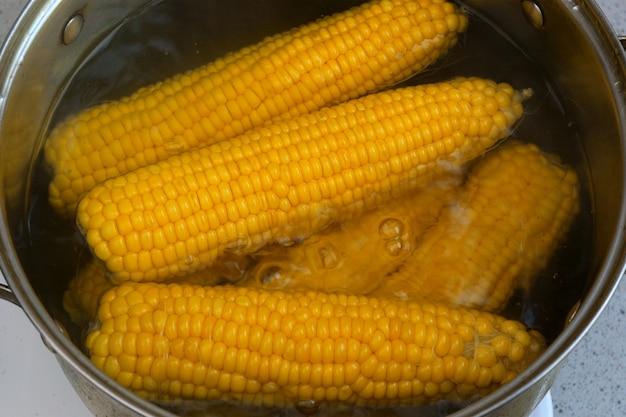 Heldere sappige gele maïs, die in kokend water op het fornuisclose-up wordt gekookt. heerlijke jonge zoete suikermaïs. zomer gezonde groenten met vitamines.